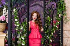 Sensueel roodharige jong meisje die zich bij de poort op bloemenbackgr bevinden Royalty-vrije Stock Foto's
