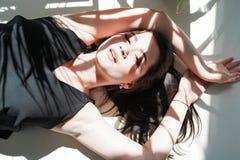 Sensueel vrouwenportret die op witte zonnige achtergrond in zwart ondergoed leggen royalty-vrije stock afbeeldingen