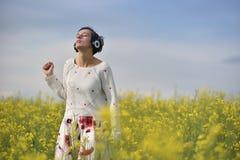 Sensuele dame die aan muziek in hoofdtelefoons luisteren en in een cano dansen Stock Foto's