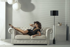 Sensuele donkerbruine dame die bij luxelaag liggen Royalty-vrije Stock Afbeeldingen