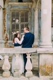 Sensuele echtgenoot en vrouw die dichtbij balustrade in antiquiteit geruïneerd paleis koesteren Achter mening royalty-vrije stock fotografie