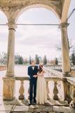 Sensuele echtgenoot en vrouw die onder overwelfde galerij in antiquiteit geruïneerd paleis koesteren stock afbeeldingen