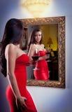 Sensuele elegante jonge vrouw in rode kleding en binnenschot Stock Afbeeldingen