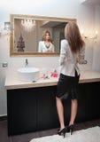 Sensuele elegante vrouw die in bureauuitrusting een grote spiegel onderzoeken. Mooie en sexy blonde jonge vrouw die wit jasje drag stock foto