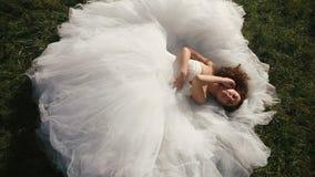 Sensuele jonge bruid in schitterende witte huwelijkskleding die op groen grasgazon liggen en seductively de camera bekijken stock footage