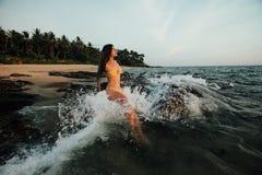Sensuele jonge donkerbruine schoonheid die geel zwempak met mooie haarzitting dragen op steen bij het strand Royalty-vrije Stock Foto