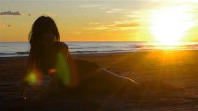 Sensuele jonge donkerbruine vrouw ontspannen zitting op een zandig strand bij zonsondergang stock videobeelden