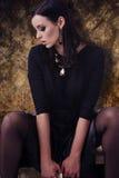 Sensuele mannequin in zwarte kleren met juwelen over gouden patroonachtergrond Stock Afbeeldingen