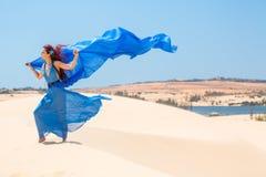 Sensuele vrouw in blauw op zand stock afbeelding