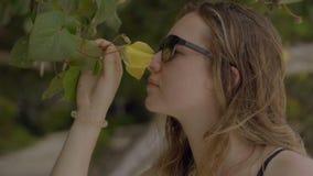 Sensuele vrouw die sunglasess ruikende bloem over tropische installatiesachtergrond dragen Het concept van reisazië stock videobeelden
