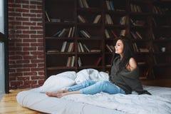 Sensuele vrouw met donker haar in groene sweater en jeans die op een bed zitten royalty-vrije stock fotografie
