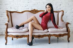 Sensuele vrouw met het perfecte lichaam stellen in een rode korte kleding Stock Fotografie