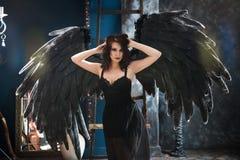 Sensuele vrouw in zwart engelenkostuum Stock Fotografie