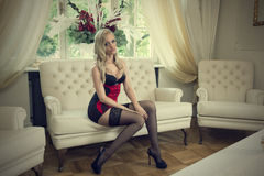Sensul woman sitting on sofa in lingerie Royalty Free Stock Images