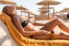 Sensuous slim woman applying suntan oil. Sensuous slim woman applying suntan lotion oil to her body at the beach Stock Photo