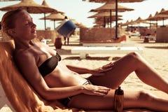 Sensuous slim woman applying suntan oil. Sensuous slim woman applying suntan lotion oil to her body at the beach Royalty Free Stock Photo