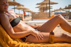 Sensuous slim woman applying suntan oil. Sensuous slim woman applying suntan lotion oil to her body at the beach Royalty Free Stock Image