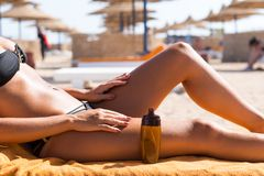 Sensuous slim woman applying suntan oil. Sensuous slim woman applying suntan lotion oil to her body at the beach Stock Photography