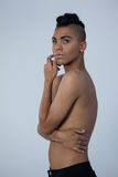 Sensuous transgender woman looking away. While standing against gray background Stock Photos