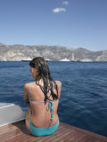 Sensuous Wet Woman In Swimsuit Sitting On Yacht. Rear view of sensuous wet woman in swimsuit sitting on yacht's floorboard Royalty Free Stock Photos