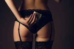 Sensuous woman holding condom. Sexy slut in stockings waiting for sex. Woman buttocks in black lingerie Royalty Free Stock Images