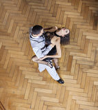 Sensuous Woman And Man Performing Tango On Hardwood Floor. High angle view of sensuous young women and men performing tango on hardwood floor at restaurant Stock Image