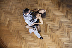 Sensuous Woman Performing Tango With Partner At Restaurant. High angle view of sensuous young women performing tango with male partner on hardwood floor at Royalty Free Stock Photography