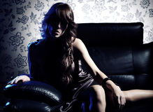Sensuous Woman Sitting On Leather Seat. Young sensuous woman sitting on leather seat against wallpaper Royalty Free Stock Images