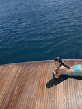 Sensuous Woman In Swimsuit Relaxing On Yacht. High angle view of sensuous woman in swimsuit relaxing on yacht's floorboard Stock Photo