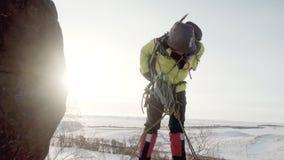 Sentándose en la repisa nevosa de la montaña, el escalador comprueba la integridad de su mochila, cuerda del paquete, ganchos, y almacen de metraje de vídeo