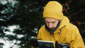 Sentándose la colina de la montaña al lado de los árboles verdes un hombre joven está buscando un nuevo camino E almacen de metraje de vídeo