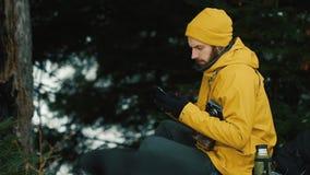 Sentándose la colina de la montaña al lado de los árboles verdes un hombre joven está utilizando un teléfono almacen de video
