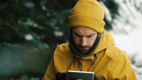 Sentándose la colina de la montaña al lado de los árboles verdes un hombre joven está utilizando una tableta metrajes