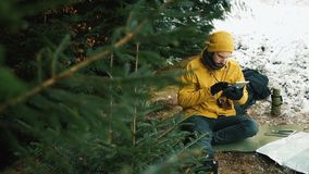 Sentándose la colina de la montaña al lado de los árboles verdes un hombre joven está utilizando una tableta almacen de metraje de vídeo