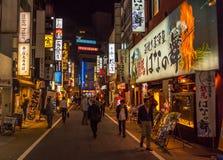 Sent - nattplats av folk som går på en shoppinggata i Shinjuku Tokyo Royaltyfri Bild