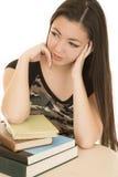 Sentada adolescente americana asiática en el escritorio con los libros de escuela Imagen de archivo