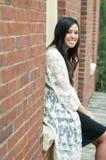 Sentada adolescente atractiva en ventana Imagenes de archivo