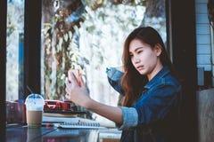 Sentada adolescente de Asia solamente usando el teléfono móvil con el selfie en café Fotos de archivo