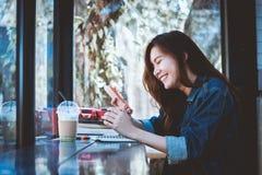 Sentada adolescente de Asia solamente usando el teléfono móvil con la sonrisa en café Imagen de archivo