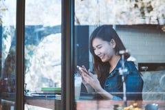 Sentada adolescente de Asia solamente usando el teléfono móvil con la sonrisa en café Foto de archivo libre de regalías