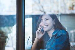 Sentada adolescente de Asia solamente usando el teléfono móvil con la sonrisa en café Fotografía de archivo libre de regalías
