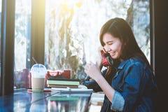 Sentada adolescente de Asia solamente usando el teléfono rojo con la sonrisa Fotografía de archivo