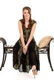 Sentada adolescente de la moda en un banco negro Imagenes de archivo