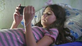 Sentada adolescente de la muchacha bonita en el sofá y usar smartphone del teléfono móvil almacen de metraje de vídeo