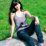 Sentada adolescente de la sonrisa en la piedra Foto de archivo libre de regalías