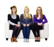 Sentada adolescente de tres muchachas en el sofá Foto de archivo