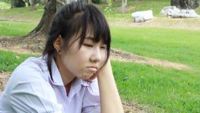 Sentada adolescente del estudiante tailandés infeliz triste en parque almacen de video