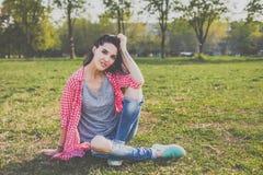 Sentada adolescente del inconformista en el prado verde Imagen de archivo