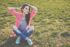 Sentada adolescente del inconformista lindo en el prado verde Imagen de archivo