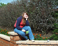 Sentada adolescente en la canillera del jardín Fotografía de archivo libre de regalías